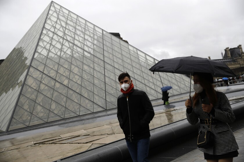 Tourists wearing a mask walks away from the Louvre museum in Paris, Monday, March 2, 2020. The Louvre Museum was closed again Monday as management was meeting with staff worried about the spread of the new virus in the world's most-visited museum. (AP Photo/Christophe Ena)