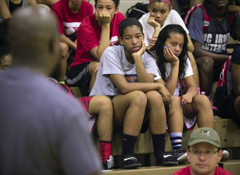 Tailah Hooker and Mikayla Nash, along with others listen to Will Moreland, one of the guest speakers during the Increase the Peace, Stop the Violence Blacktop Classic, at the Jackie Robinson Family YMCA in Mountain View which included guest speakers taking about their personal experiences, and how to stop violence and bullying in schools and the community. It also featured basketball games.