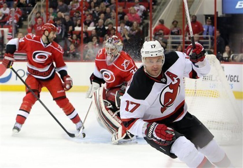 New Jersey Devils' Illya Kovalchuk (17), of Russia, skates away after scoring against the Carolina Hurricanes' Dan Ellis, center, and Jay Harrison, left, during the first period of an NHL hockey game in Raleigh, N.C., Saturday, March 9, 2013. (AP Photo/Ted Richardson)