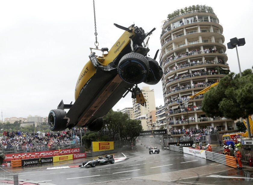 The car of Renault driver Jolyon Palmer of Britain is removed from the circuit after crashing during the Formula One Grand Prix at the Monaco racetrack in Monaco, Sunday, May 29, 2016. (AP Photo/Petr David Josek)