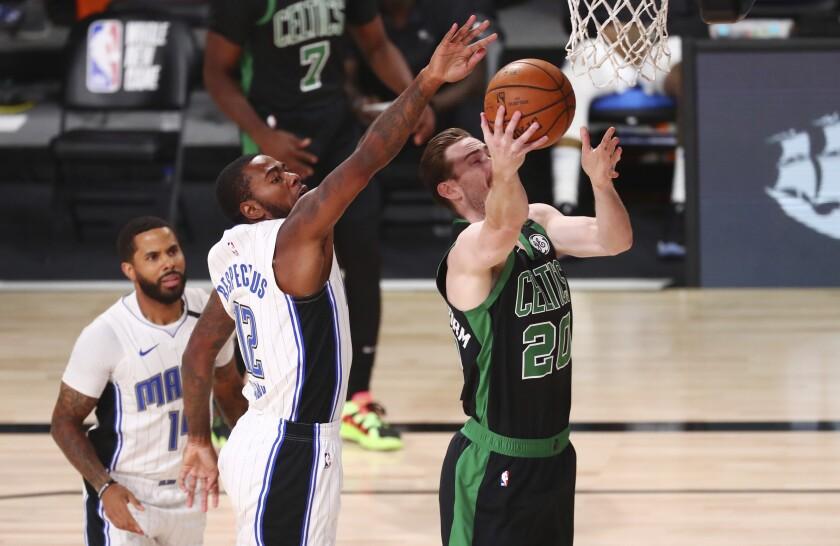 Gordon Hayward (20), de los Celtics de Boston, encesta al dejar atrás a Gary Clark (12), del Magic
