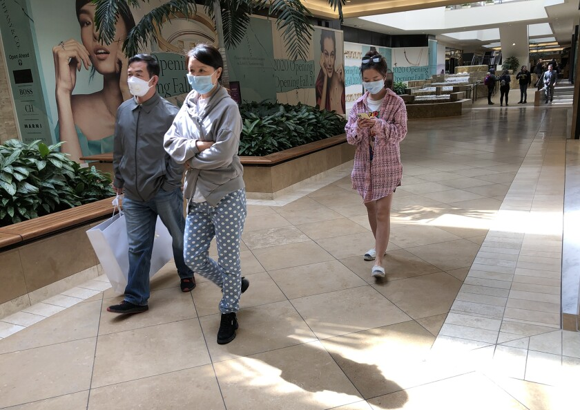 Shoppers wear masks as they walk through South Coast Plaza in Costa Mesa on Monday.