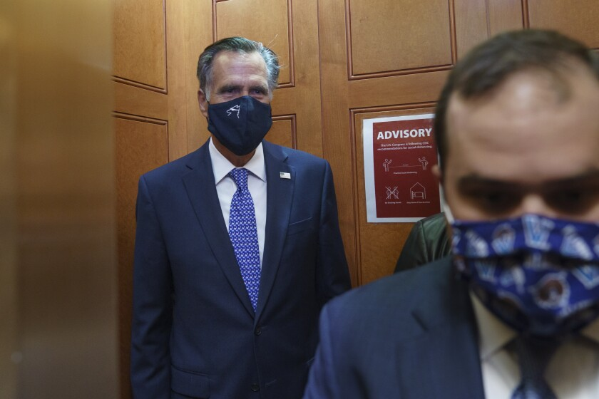 Sen. Mitt Romney leaves the Senate Chamber after a procedural vote at the Capitol.