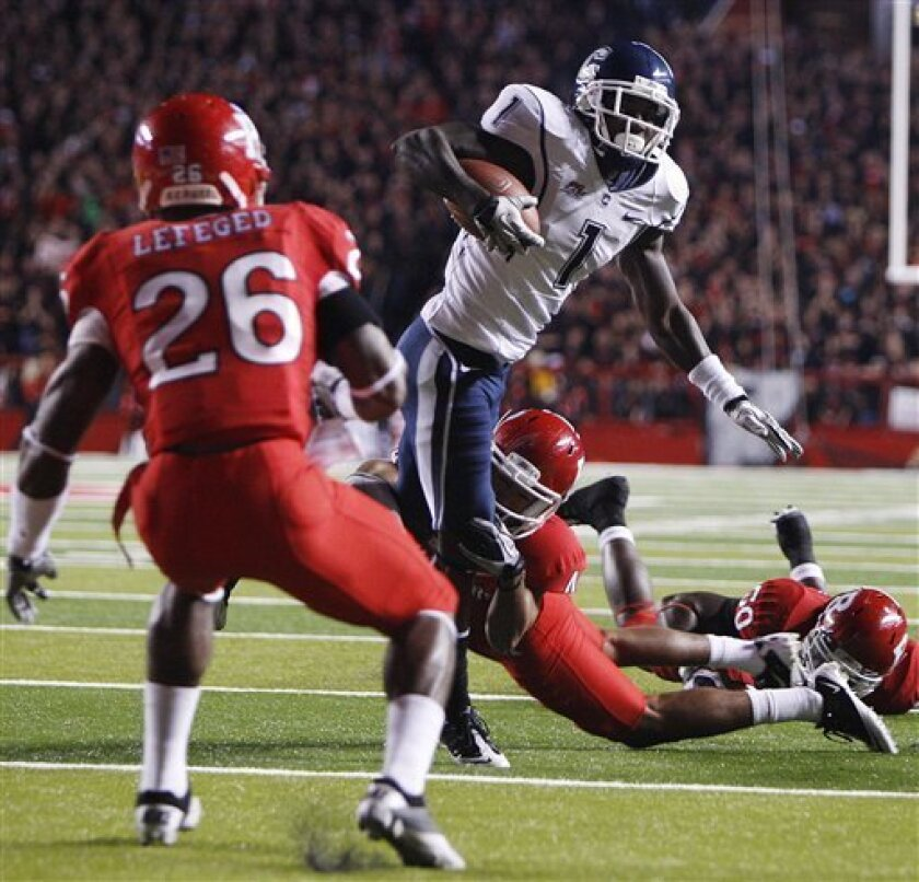 Connecticut's Dwayne Difton (1) tries to get away from Rutgers' David Rowe (4) and Joe Lefeged (26) during the first half of an NCAA college football game in Piscataway, N.J., on Friday, Oct. 8, 2010. (AP Photo/Tim Larsen)
