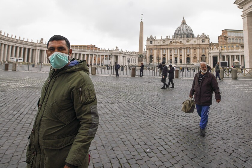 A man wearing a mask walks in St. Peter's Square at the Vatican, Friday, March 6, 2020. A Vatican spokesman has confirmed the first case of coronavirus at the city-state. Vatican spokesman Matteo Bruni said Friday that non-emergency medical services at the Vatican have been closed so they can be sanitized following the positive test on Thursday. (AP Photo/Andrew Medichini)