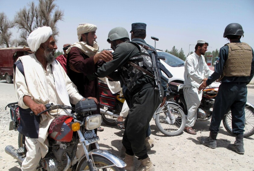 Afghan police officers search commuters at a checkpoint in Helmand province on June 25. A Taliban offensive in its fourth day in the southeastern region has killed scores of civilians and fighters.