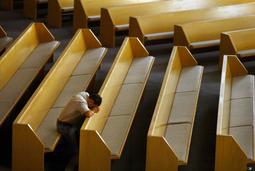 A man prays alone at an Orange County church where five priests were accused of child molestation in 2002.