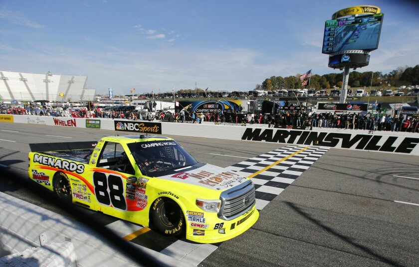 Camping World Truck Series driver Matt Crafton (88) crosses the finish line to win the NASCAR Camping World Truck auto race at the Martinsville Speedway in Martinsville, Va., Saturday, Oct. 31, 2015.    (AP Photo/Steve Helber)