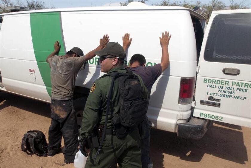 Un miembro de la Patrulla Fronteriza registra a dos jóvenes mexicanos antes de subirlos a la camioneta. EFE/Archivo