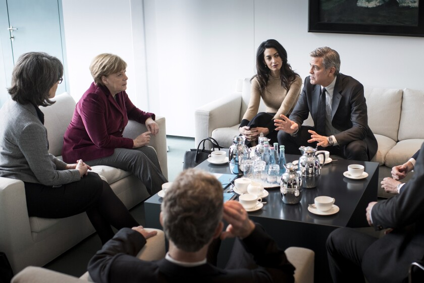 Chancellor Angela Merkel, second from left, meets with Amal and George Clooney and others in Germany on Friday.