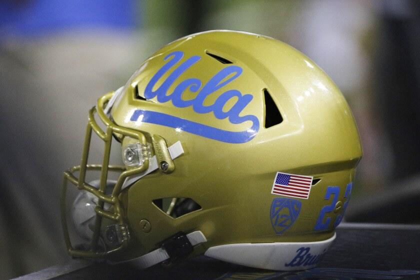A UCLA helmet sits on the sideline.