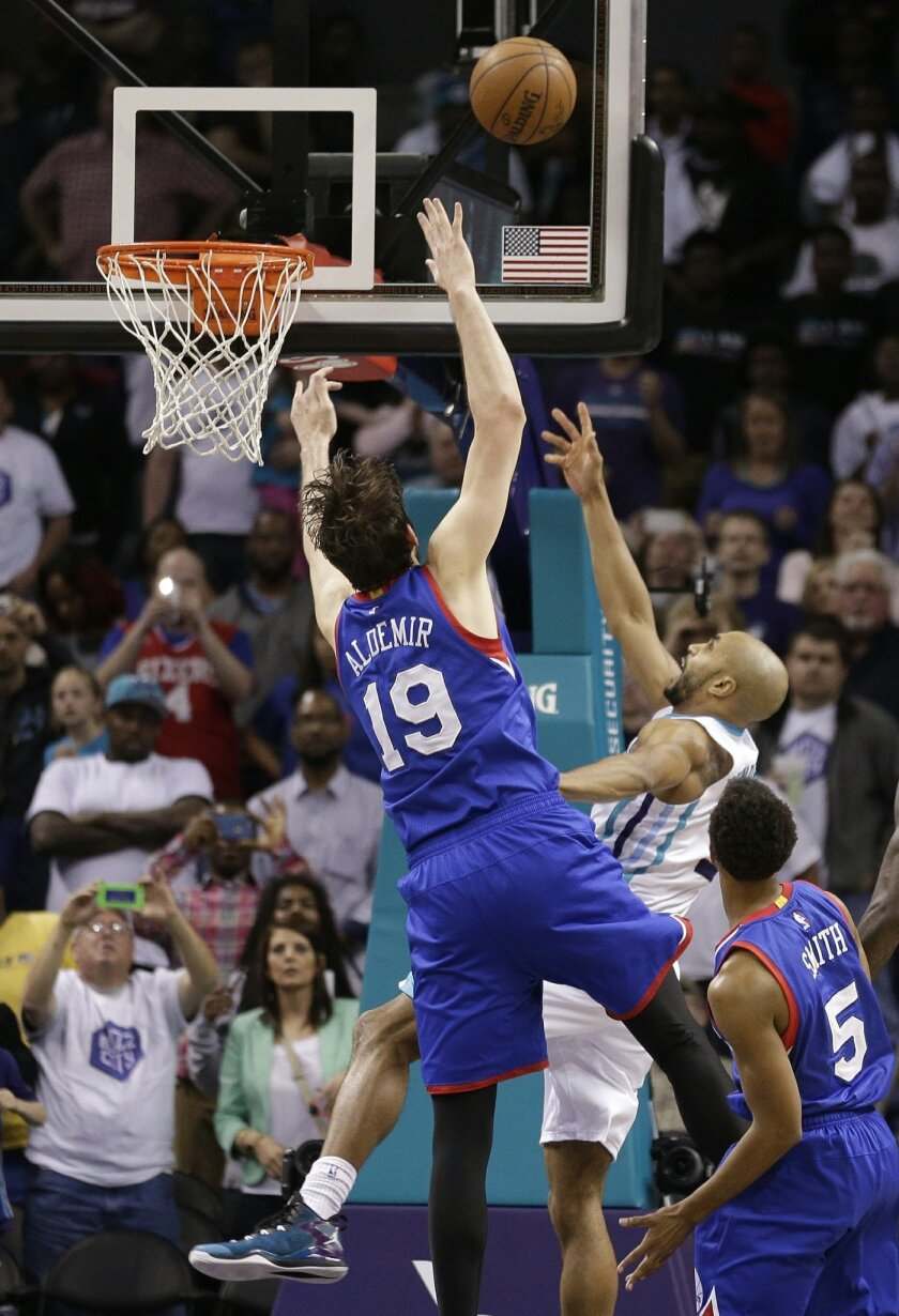 Charlotte Hornets' Gerald Henderson, center, shoots over Philadelphia 76ers' Furkan Aldemir, left, and Ish Smith, right, for the go-ahead and eventual game-winning basket during the second half of an NBA basketball game in Charlotte, N.C., Saturday, April 4, 2015. The Hornets won 92-91. (AP Photo/Chuck Burton)