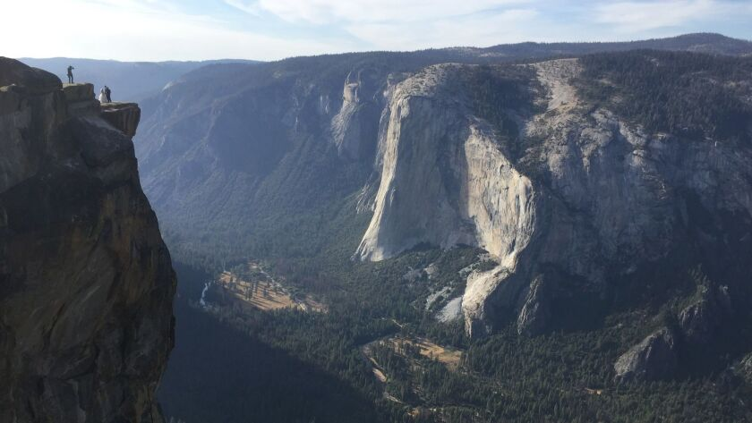 A couple on their wedding day are seen being photographed at Taft Point in California's Yosemite National Park in September. A Yosemite park official said Thursday that two visitors have died in a fall from the popular overlook.