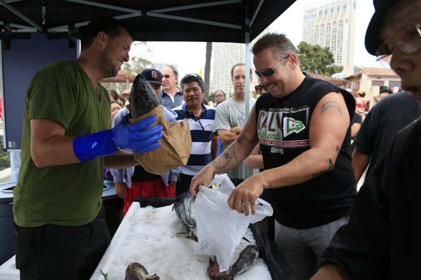 August 2nd, 2014 San Diego, CA- Fisherman Zach Roach Jr. prepares to place a black cod into a bag held by customer Brent Thompson on Saturday, the first day of San Diego's Tuna Harbor Dockside Market. Photo by David Brooks/ U-T San Diego MANDATORY PHOTO CREDIT DAVID BROOKS / U-T SAN DIEGO; ZUMA Pre