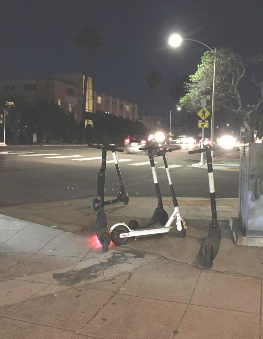 These 'resting' electric scooters, photographed last week, block access to the public sidewalks in the Village of La Jolla. (Photo submitted by a La Jolla Light reader.)