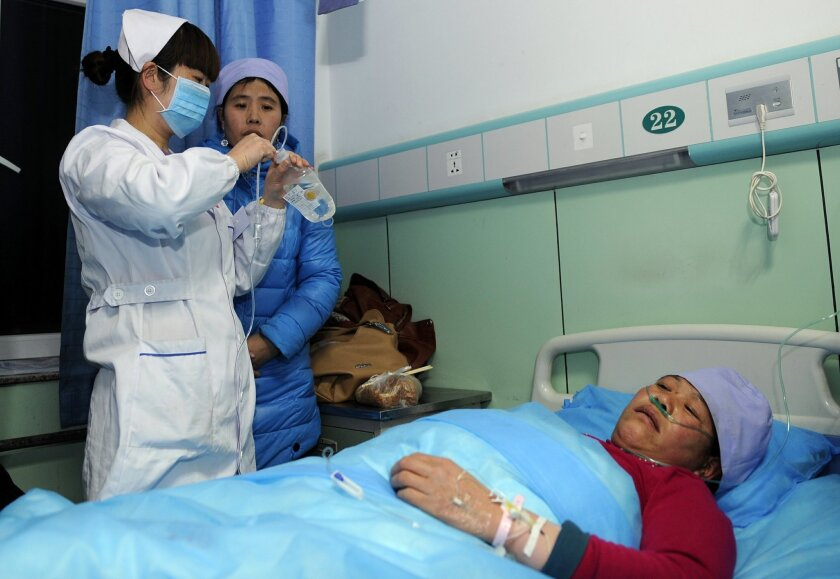 In this Sunday, Jan. 5, 2014 photo provided China's official Xinhnua News Agency, an injured woman receives medical treatment at a hospital in Xiji Town of Guyuan, northwest China's Ningxia region. China's Xinhua News Agency said Monday, Jan. 6, 14 people were killed in a stampede at a mosque in the country's north and 10 other people were injured in the incident in Guyuan. (AP Photo/Xinhua, Li Ran) NO SALES