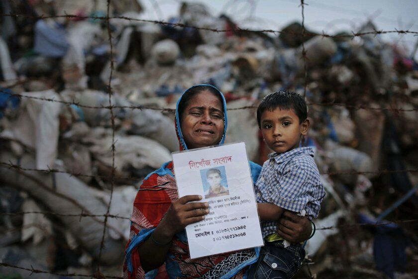 FILE - In this Friday, June 14, 2013 file photo, Bangladeshi Maksuda holds a picture of her son Mehedi who was a garment worker and is missing following the collapse of the Rana Plaza building as she poses next to the rubble in Savar, near Dhaka, Bangladesh. A delegation of the U.S. Trade Representative's office is on a five-day visit to Bangladesh ending Wednesday, Sept. 23, 2015, to see the improvement of safety standards at factory sites and changes to legal documents allowing for wider workers' rights, key conditions for regaining the Generalized System of Preferences facility under which the United States allows imports of more than 5,000 goods from 122 of the world's poorest countries with low or zero-tariff benefits. The trade benefit was withdrawn after the collapse of Rana Plaza, a building complex housing five garment factories outside the capital, Dhaka in 2013. The garment industry is crucial to Bangladesh's economy as it employs about 4 million workers, mostly rural women, and many other sectors including banks are heavily dependent on it. (AP Photo/Kevin Frayer, File)