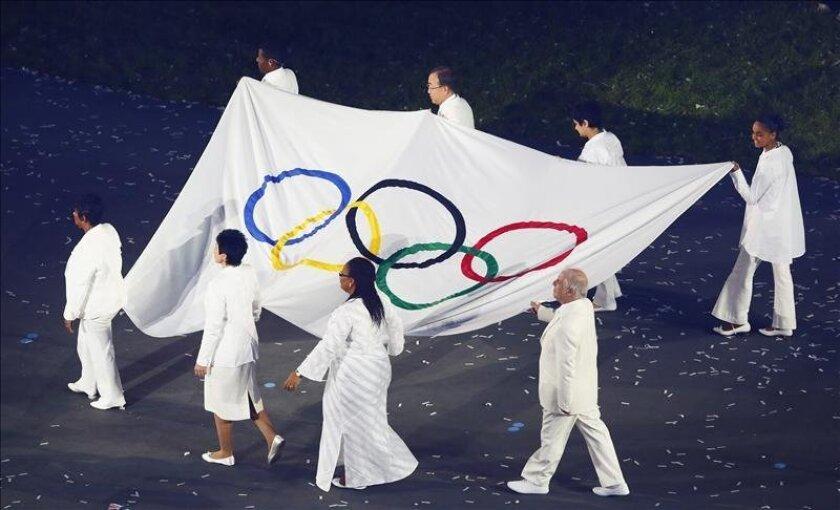 Varias personas llevan la Bandera Olímpica. EFE/Archivo