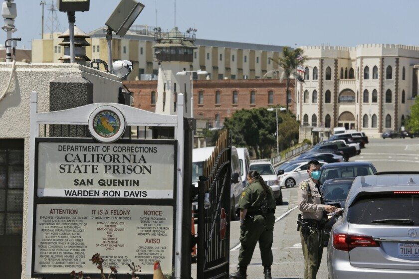 FILE - In this July 9, 2020, file photo, a correctional officer checks a car entering the main gate of San Quentin State Prison in San Quentin, Calif. A federal judge on Thursday, July 29, 2021, said he will consider ordering all California prison employees and inmate firefighters to be vaccinated as the state tries to head off another coronavirus infection surge driven by the delta variant. (AP Photo/Eric Risberg, File)