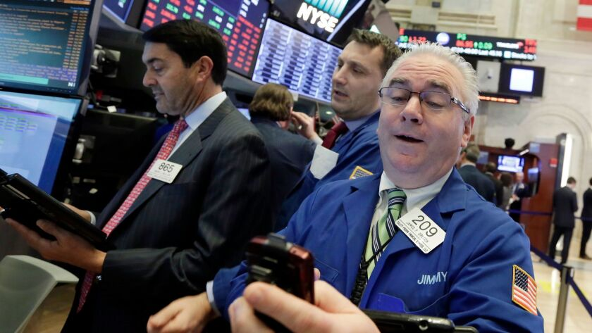Stocks bounced back in the last hour of trading, with gains by technology companies outweighing losses in healthcare and other sectors. Above, traders work on the floor of the New York Stock Exchange.