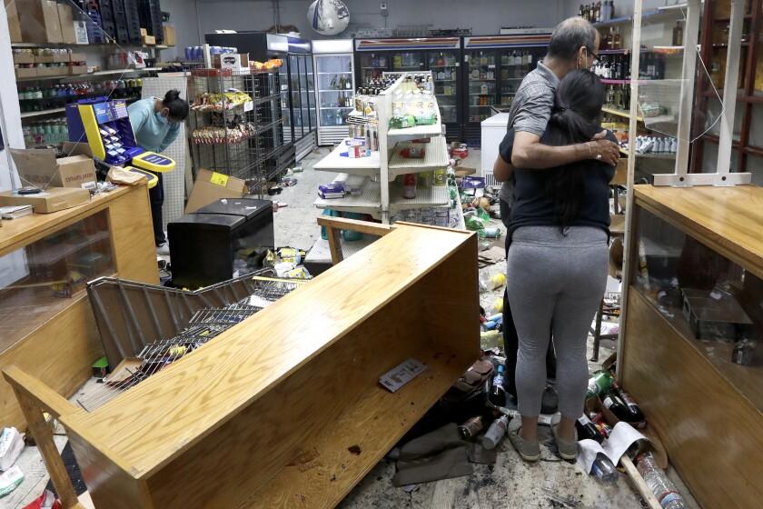 Yogi Dalal hugs daughter Jigisha Monday at their looted food and liquor store