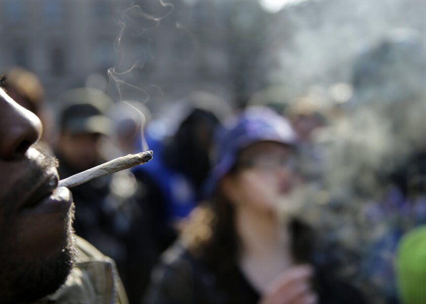 A new study finds that people who use drugs only on weekends only are more likely than not to be using drugs on weekdays too in six months' time. Pictured here, a man smoking marijuana outside the New Jersey state house.
