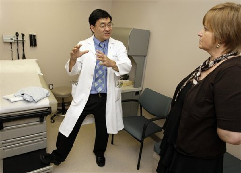 In this Wednesday May 27, 2009 photo, Dr. Patrick Hwu, left, talks with his cancer patient Hilde Stapleton during an examination at The University of Texas MD Anderson Cancer Center in Houston. Stapleton has been receiving an experimental treatment for melanoma. (AP Photo/David J. Phillip)