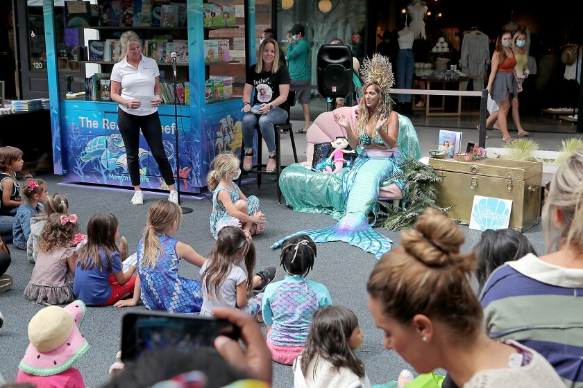 A member of the H.B. Mermaids speaks during the grand opening for the Reading Reef library at Pacific City.