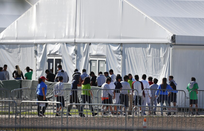 Children line up to enter a tent at the Homestead Temporary Shelter for Unaccompanied Children in Homestead, Fla.