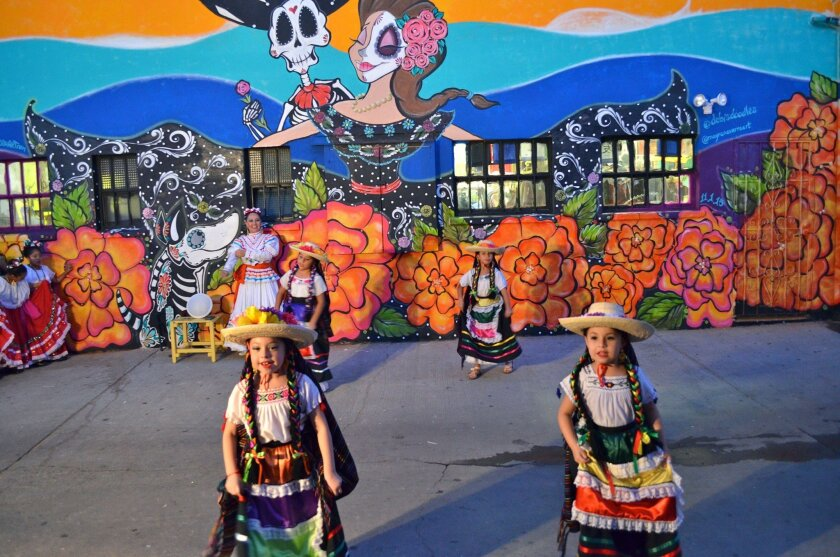 Girls in colorful dresses perform folk dances on Nov. 1 at the launch of the Alleyway Activation Program, an effort to spruce up downtown Encinitas alleys.