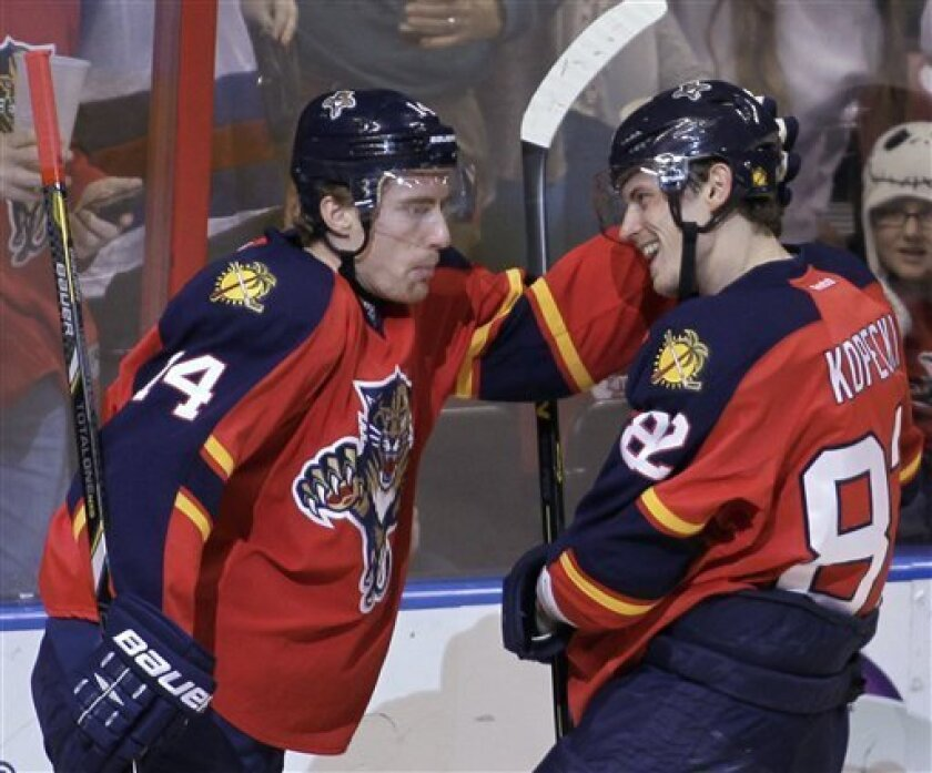 Florida Panthers' Tomas Kopecky (82), of Slovakia, celebrates with teammate Tomas Fleischmann (14), of the Czech Republic, after Kopecky scored against the Pittsburgh Penguins during the first period of an NHL hockey game, Tuesday, Feb. 26, 2013, in Sunrise, Fla. (AP Photo/Luis M. Alvarez)