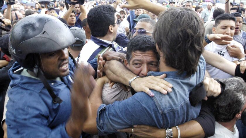 Civilians give protection to an alleged follower of Venezuelan President Hugo Chavez who took part i