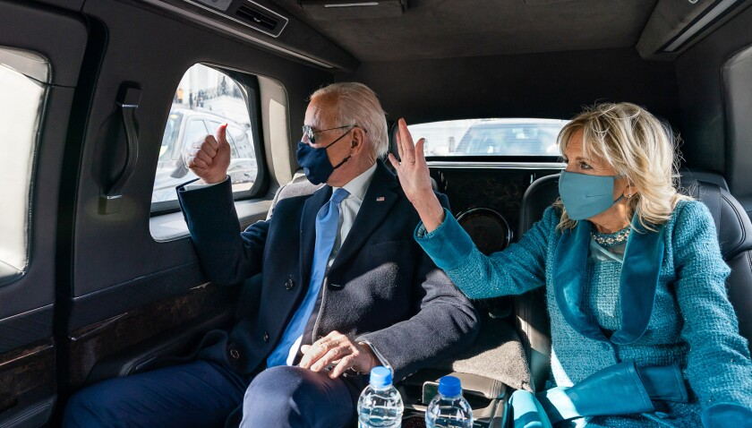 President Biden and First Lady Jill Biden wave as they ride in the presidential limousine Jan. 20.