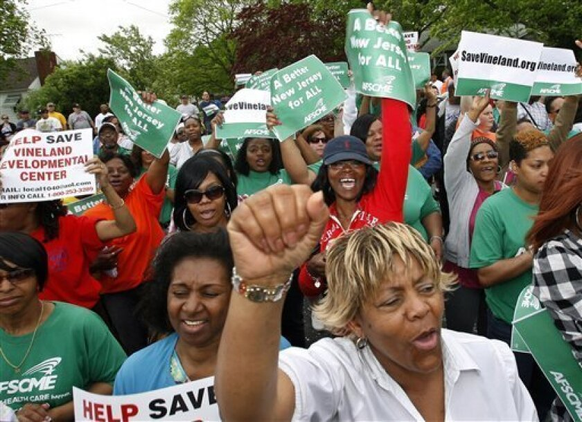 FILE - In this April 26, 2011 file photo, worker Marion Gaines, front right, reacts with others in a large gathering of workers and supporters as they listen to Rev. Al Sharpton, in Vineland, N.J., outside the Vineland Development Center which houses 350 women with severe disabilities. New Jersey G