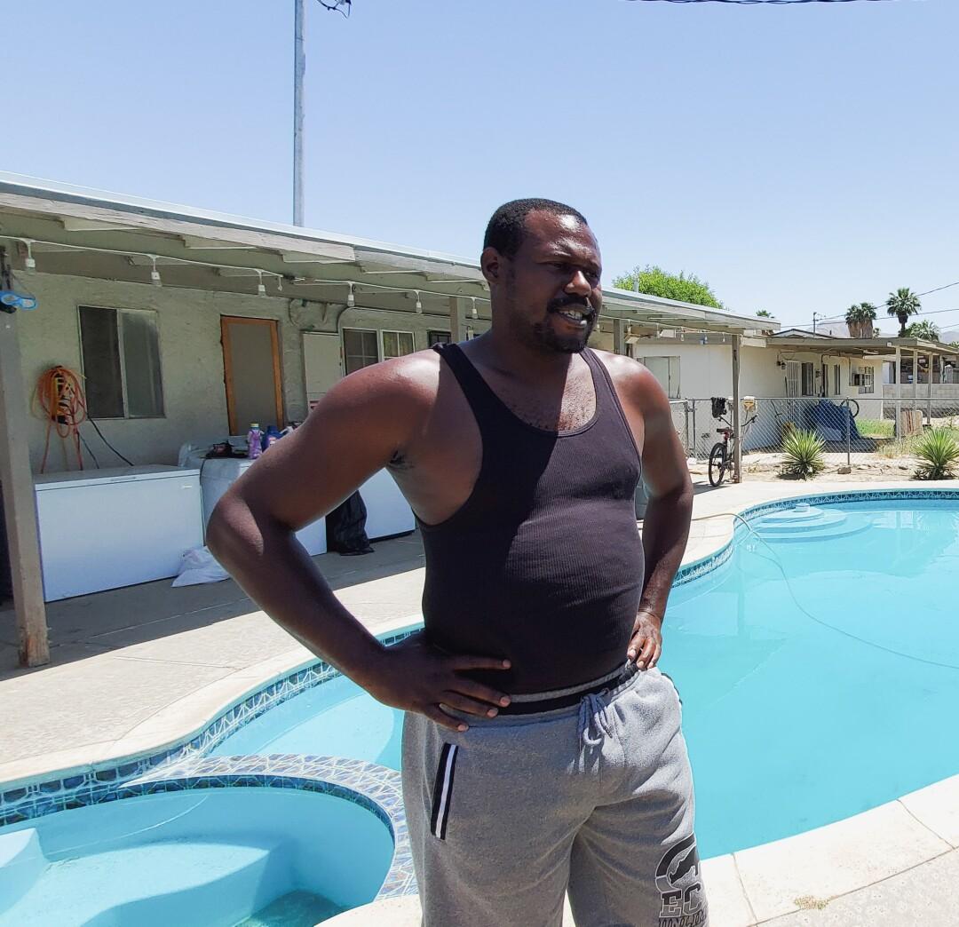 A man standing next to a backyard swimming pool