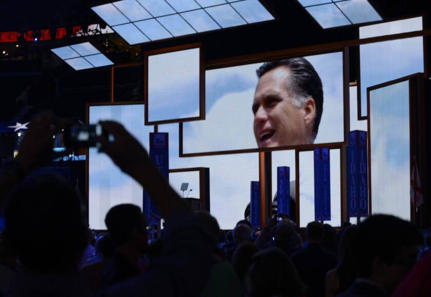 Delegates watch campaign videos of presidential candidate Mitt Romney after the chairman of the Republican National Convention Reince Priebus gaveled the convention to order in Tampa, Fla.