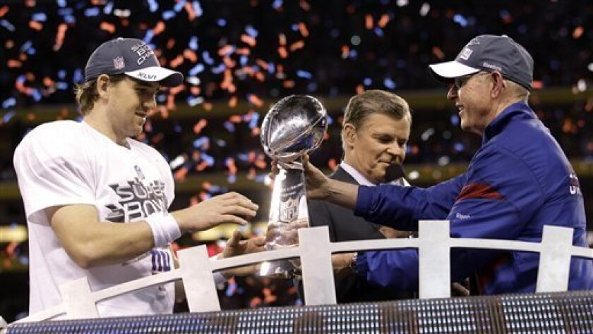 New York Giants head coach Tom Coughlin, right, hands the Vince Lombardi Trophy to quarterback Eli Manning after their 21-17 win over the New England Patriots in the NFL Super Bowl XLVI football game, Sunday, Feb. 5, 2012, in Indianapolis. (AP Photo/David J. Phillip)