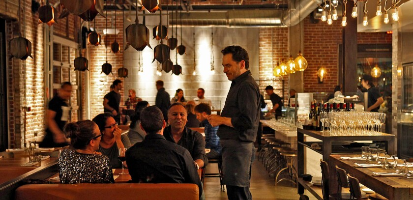 A waiter talks with a table at Bestia, the Italian restaurant from restaurateur Bill Chait and husband-and-wife team Ori Menashe and Genevieve Gergis.