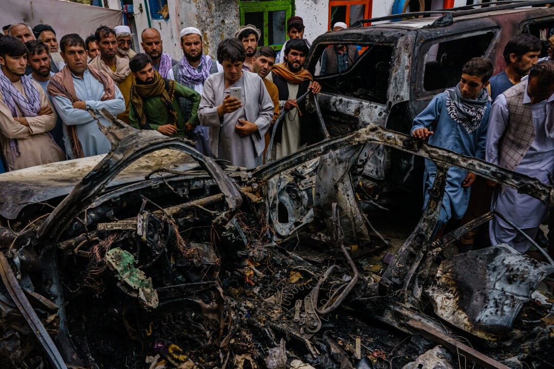 People gathering around burned-out vehicle