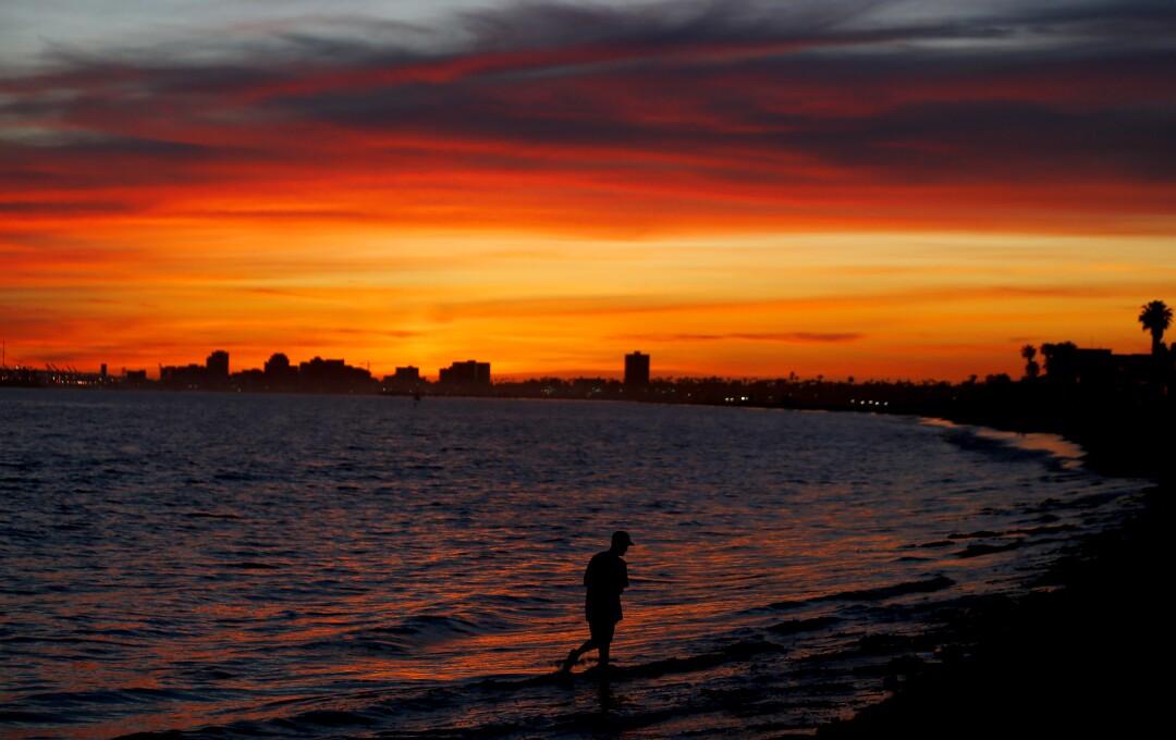 A beachgoer walks along the shoreline in Long Beach.