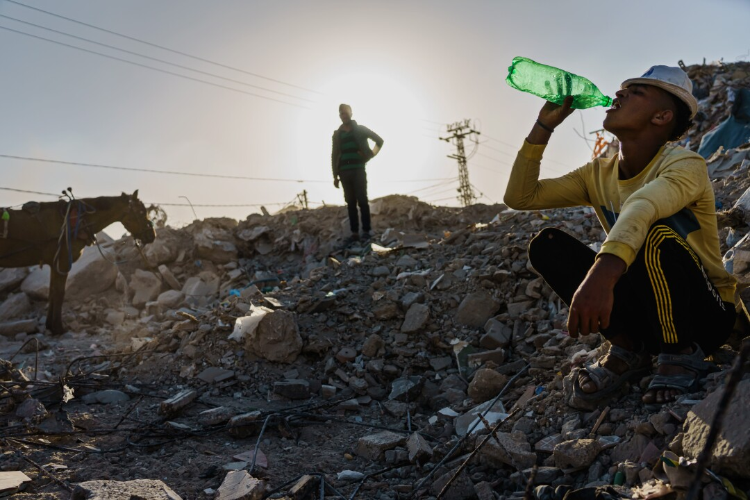 A worker drinks from a bottle during a break on a rubble pile