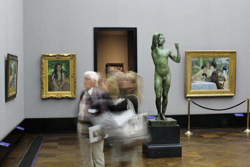 In this photo taken with a long shutter, members of the media walks through the exhibition 'Impressionism - Expressionism. Turning Point in Art' during the press preview at the Alte Nationalgalerie (Old National Gallery), in Berlin, Germany, Wednesday, May 20, 2015. The paintings from left: Le Pont de Chatou by Maurice de Vlaminck, L'Ete by Auguste Renoir, the sculpture L'Age d'airain by Auguste Renoir and the painting Chez le pere Lathuille by Edouard Manet. The exhibition opens on May 22, and runs through Sept. 20, 2015. (AP Photo/Markus Schreiber)