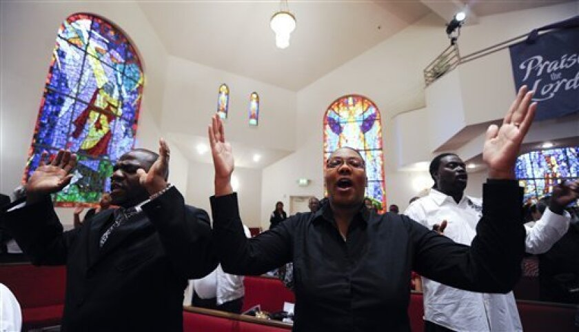 In a Wednesday, Aug. 31, 2011 photo, Rev. Kevin Kinder and his wife Quilla sing during a prayer meeting at Southern Missionary Baptist Church in Los Angeles. At churches, shopping centers, schools, and local Tea Party meetings in California, fired-up volunteers have started gathering signatures for a ballot referendum that would repeal the nation's first law requiring public schools to include prominent gay people and gay rights milestones in school lessons. (AP Photo/Chris Carlson)