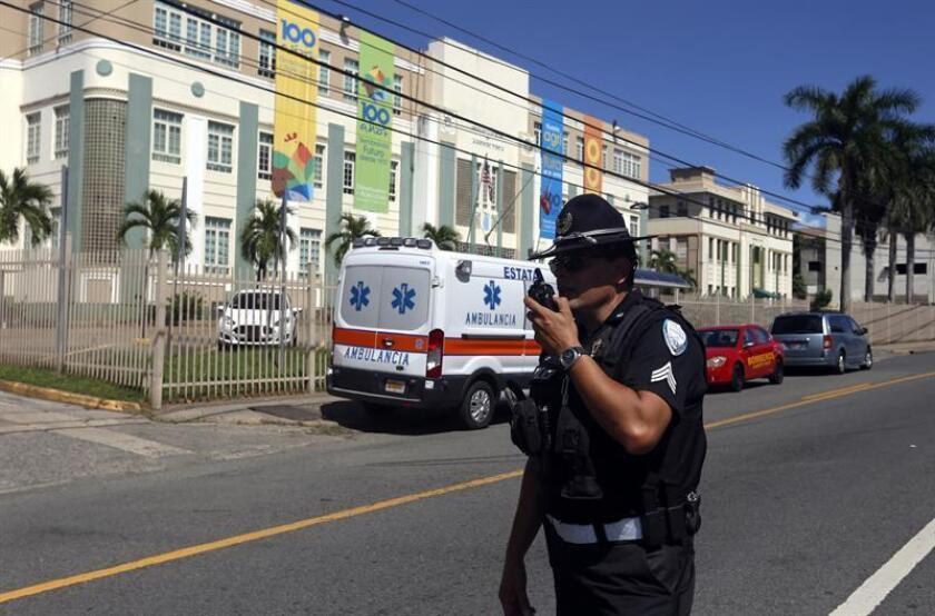 Un policía vigila los alrededores del Departamento de Agricultura de Puerto Rico, durante el suceso creado por Nirma Martínez Álvarez, una empleada que amenazaba con lanzarse al vacío, el miércoles 12 de septiembre de 2018, en la azotea del edificio del Departamento situado en Santurce. EFE/Archivo