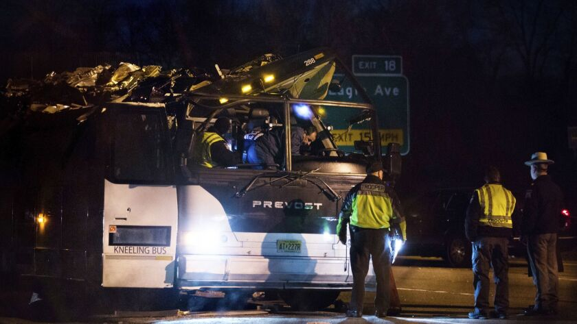 A bus that was carrying teenage passengers sits on the side of a highway after it hit an overpass on the Southern State Parkway in Lakeview, N.Y.