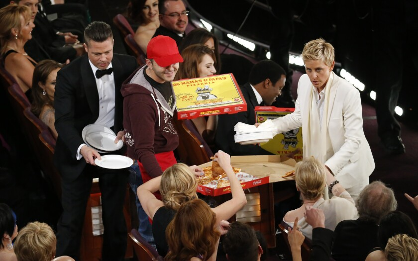 Ellen DeGeneres distributes pizza and Brad Pitt hands out paper plates in one of the host's informal bits. She seemed to forget how unwieldy the show is.