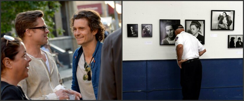 """Left photo: Actor/producer Brad Pitt, left, and actor Orlando Bloom attend the Paris Photo Los Angeles private preview at Paramount Studios on Thursday in Hollywood. Right: A firefighter examines victim pictures that are part of the """"Unedited! LAPD Photo Archives"""" exhibit at Paris Photo Los Angeles."""