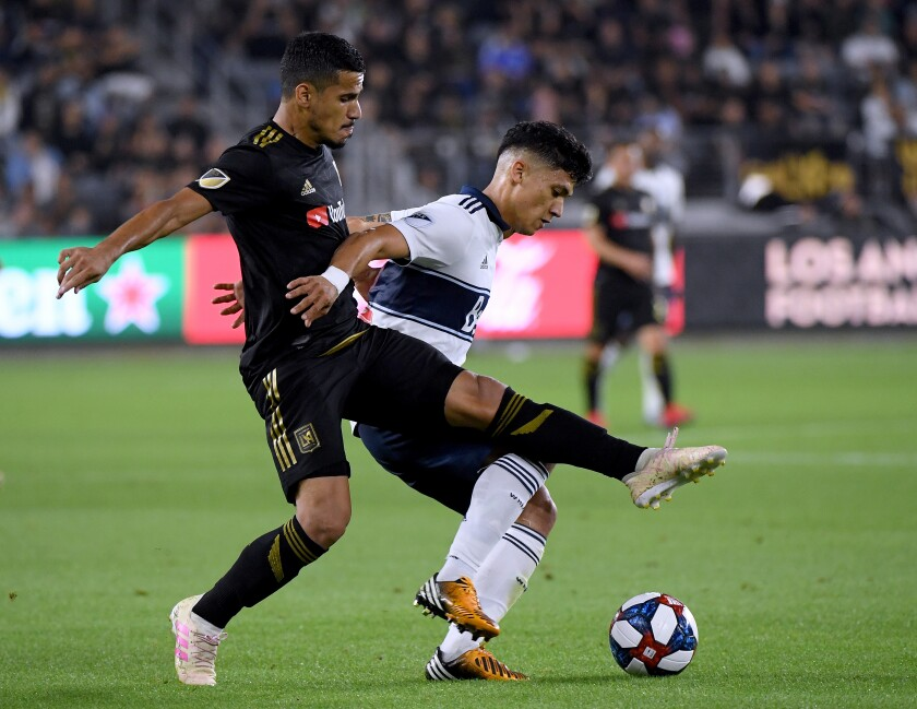 LAFC's Mohamed El-Munir, left, battles Vancouver's Fredy Montero on July 6.