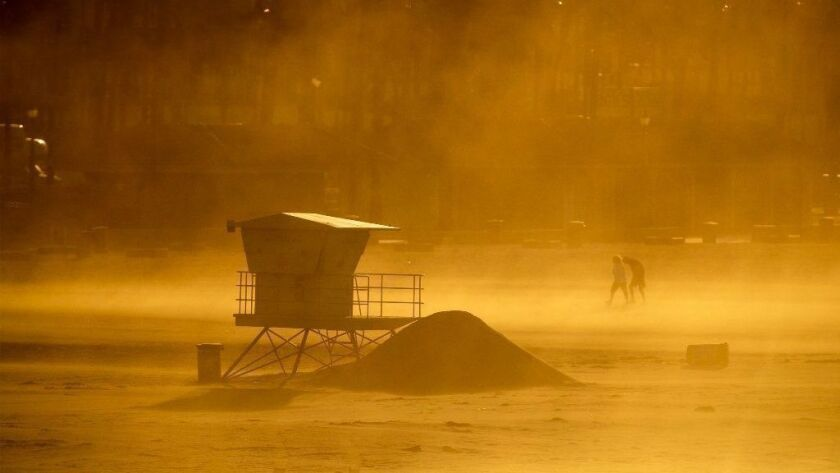 Santa Ana winds blow up sand against a lifeguard station at Huntington State Beach on Monday.