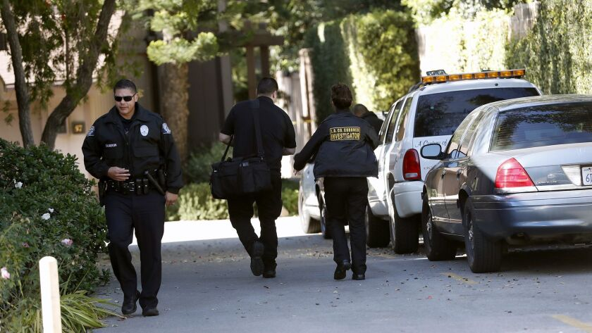 Los Angeles County coroner investigators arrive at a home in La Crescenta where a body was found that may be linked to another body found on the westbound 134 freeway early Wednesday morning.